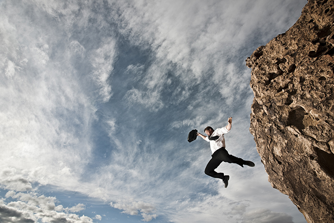 A Businessman Jumping Off A Cliff