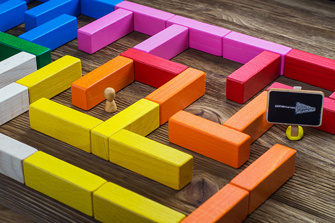 Man In The Labyrinth, The Search For The Exit. Labyrinth Of Colorful Wooden Blocks, Tetris. The Man In The Maze. The Concept Of A Business Strategy, Analytics, Search For Solutions, The Search Output.