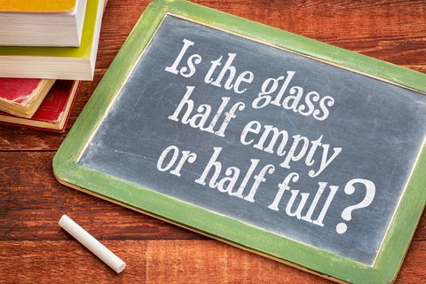 Is The Glass Half Empty Or Half Full Question On A Slate Blackboard With A White Chalk And A Stack Of Books Against Rustic Wooden Table